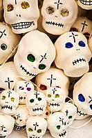 Pile of white skulls with glitter eyes and crosses, displayed in booth, Day of the Dead celebration  Guanajuato, Mexico