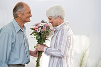 A senior man giving a senior woman flowers