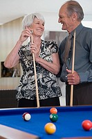 A senior couple playing pool