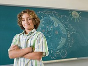 Boy standing by blackboard