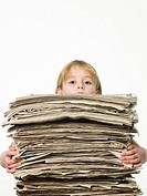 Girl holding a stack of newspapers