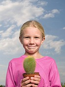 Smiling girl holding a cactus
