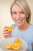 A woman holding a plate of orange segments