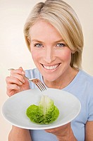 A woman holding a plate with a lettuce