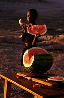 African boy eating slices of watermelon