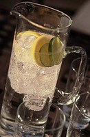 Glass Jug with fizzy water with ice cubes, lemon and lime