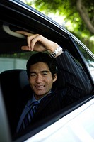 Asian businessman seated in rear passenger seat of car