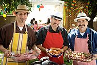 Hispanic men holding food at barbecue