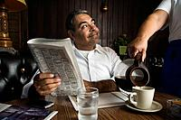 Hispanic man getting coffee at diner