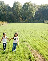Hispanic sisters holding hands in field