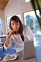 Hispanic woman eating next to laptop