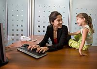 Hispanic businesswoman smiling at daughter