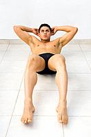 Bare_chested Hispanic man doing sit_ups