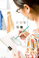 Asian female fashion designer drawing