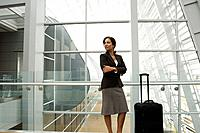 Hispanic businesswoman standing next to suitcase