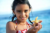 Hispanic girl holding starfish