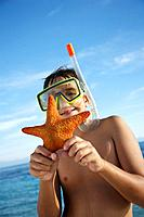 Hispanic boy holding starfish