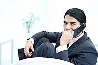 Young businessman sitting with knees up, using cell phone, looking at camera