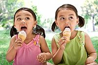 Asian sisters eating ice cream cones