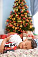 Hispanic boy sleeping in front of Christmas tree