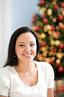 Hispanic woman in front of Christmas tree