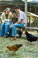 Multi_ethnic family holding bowl of eggs next to chickens