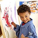 African boy painting at easel