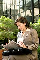 Hispanic businesswoman reading newspaper