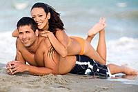 Hispanic couple laying on beach