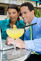 Cocktail in front of Hispanic couple looking at laptop