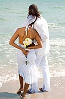 Multi_ethnic bride and groom at beach