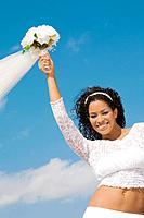 Hispanic bride holding bouquet over head