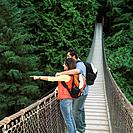 Indian couple wearing backpacks on footbridge