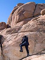African businessman climbing rock