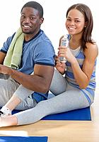 African couple sitting on yoga mat