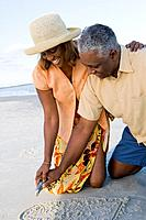 African couple writing in sand
