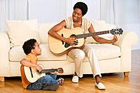 African mother and son playing guitar