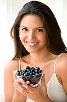 Hispanic woman holding bowl of blueberries