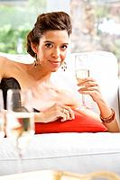 Hispanic woman holding glass of champagne