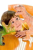 Hispanic boy playing with toy dinosaurs