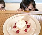 Hispanic girl children peeking over table at birthday cupcake