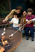 Hispanic family roasting marshmallows