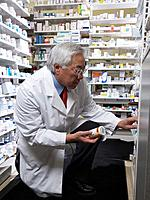 Senior Asian pharmacist looking at medication