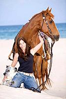 Woman on the beach with horse and dog