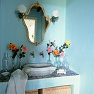 Colourful turquoise bathroom with wash basin and gilt mirror