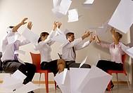 uomini e donne in ufficio lanciano fogli di carta