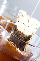 Close_up of a glass of herbal tea with a teabag being dipped in it