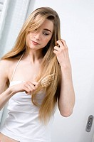 Close_up of a young woman brushing her hair