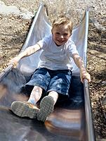 Smiling young boy on slide