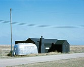 VISTA, DUNGENESS, KENT, UK, SIMON CONDER ASSOCIATES, EXTERIOR, VIEW FROM ROAD TOWARDS SEA WITH CARAVAN/GUESTROOM